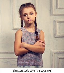 Unhappy kid girl in stylish clothing looking with sad face and folded arms on studio wall background