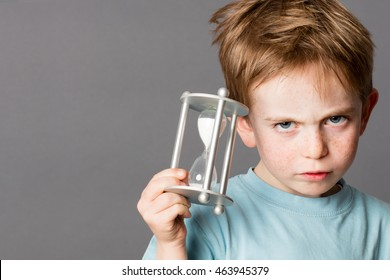 unhappy little boy with red hair showing his impatience with an egg timer in his hands for time concept, grey background
