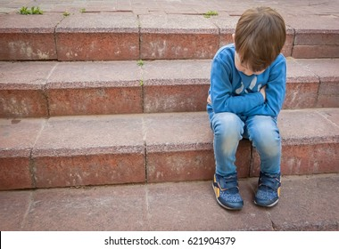 Unhappy little Caucasian child sitting on the stairs in a closed position with his head down. School bullying, kindergarten abuse, psychological childhood trauma, sad kid, stomach ache, grieving.