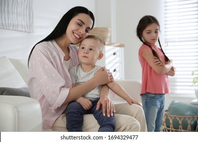 Unhappy little girl feeling jealous while mother spending time with her baby brother at home