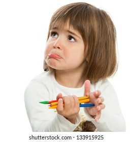 Unhappy little girl holding wax crayons.Isolated.