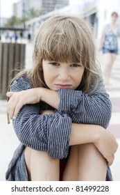 Unhappy little girl sitting on bench. Problems with parents
