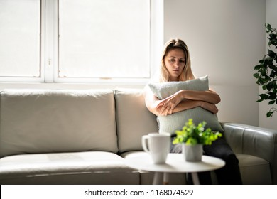 Unhappy lonely depressed woman at home living room