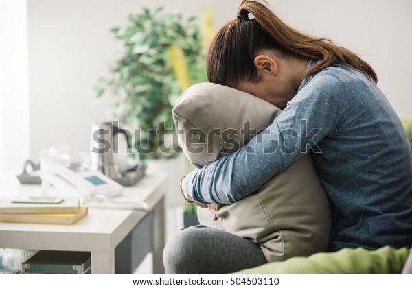 infelice donna depressa solitaria a casa, lei è seduta sul divano e nascondere il viso su un cuscino, concetto di depressione