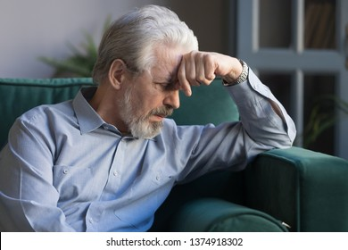 Unhappy lonely grey haired mature man sitting on couch alone, holding head on hand, sad old husband missing wife, upset middle aged male lost in thoughts, elderly and loneliness concept close up