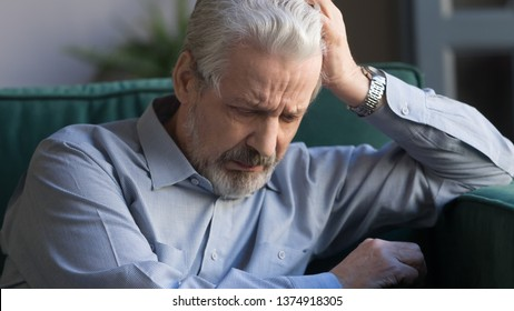 Unhappy lonely grey haired mature man sitting alone, sad old husband missing wife, upset middle aged male lost in thoughts, remembering past, elderly and loneliness concept close up horizontal banner