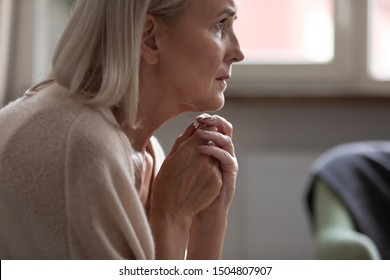 Unhappy lonely mature woman sitting alone close up, lost in thoughts, dementia or mental disorder, frustrated older female looking in distance, thinking about emotional or health problem