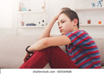 Unhappy lonely teenage boy at home, thinking about something, pubertal period, psychological problem. Lost in thoughts.
