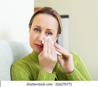 Unhappy lonely woman on sofa at home