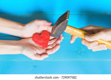 Unhappy love concept, woman holding a plasticine heart and man destroying it with a hammer.