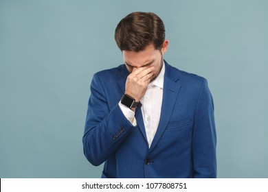Unhappy man crying, closed eyes and have a problem. Business people concept, richly and success. Indoor, studio shot on light blue background