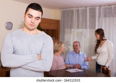 Unhappy man faced with misunderstanding big european family
