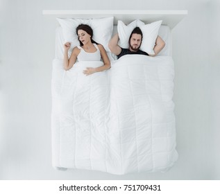 Unhappy man in his bed covering his ears with a pillow, his girlfriend is snoring