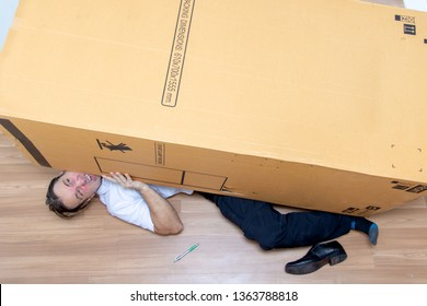 The unhappy man lying under a big box. Large cardboard fall down at the postman.