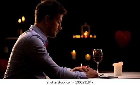 Unhappy man sitting alone in restaurant, waiting for woman, unsuccessful date