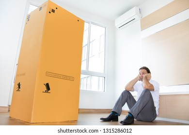 Unhappy man sitting on the floor in an empty apartment with a big cardboard box. Man is thinking about the large package in the new room.
