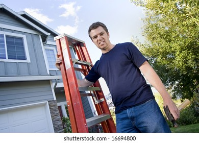Unhappy man standing in front of house holding ladder and hammer. Horizontally framed photo.