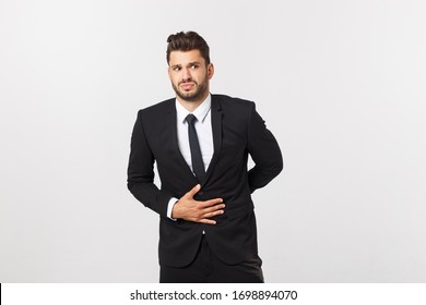 Unhappy man with stomach pain spasm. portrait of handsome bearded businessman in suit. Indoor studio shot, isolated on grey background
