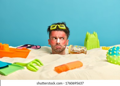 Unhappy man with suburn skin and sunscreen on nose, buried in sand, wears swimming goggles, surrounded with beach objects, poses over blue sea background. People, rest, summer, vacation concept