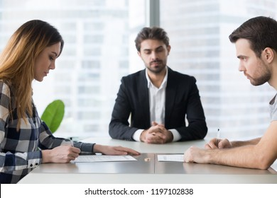 Unhappy married family young couple getting divorced in lawyers office. Husband and wife signing documents on divorce, giving permission to marriage dissolution, breaking up concept.