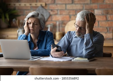 Unhappy mature couple checking financial documents, calculating domestic bills, having problem with money, upset senior man wearing glasses and woman feeling depressed about bankruptcy or debt
