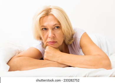 unhappy mature female with head reclined upon hands in bed at bedroom