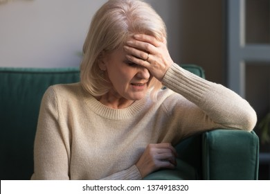 Unhappy mature grey haired woman suffering from headache, pain, touching forehead, panic attack, received bad news, depressed middle aged grandmother sitting on couch at home alone, close up