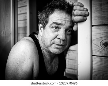 Unhappy middle aged man in t-shirt at home
