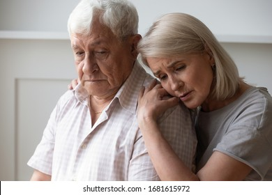 Unhappy middle-aged wife comforting depressed older husband, sad mature woman embracing unhappy senior man from back, helping overcome troubles, health problems, consoling and supporting