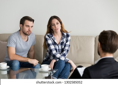Unhappy millennial couple talking to psychologist sitting on couch visiting counselor sharing problems in bad relationships at family therapy session, marriage counseling psychotherapy concept