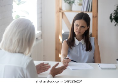 Unhappy millennial recruiter or HR agent look frustrated talking with job applicant during interview in office, doubtful young female employer or headhunter feel uncertain speaking with work candidate