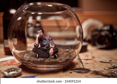 Unhappy Miniature Waiting Man Trapped inside a Fishbowl.