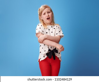 unhappy modern child in red pants with pain in hand isolated on blue background