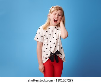 unhappy modern girl in red pants with a earache on blue background
