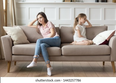 Unhappy mother and stubborn preschool daughter sitting separately on couch, offended mum and upset child little girl ignoring each other after quarrel, family generations problem conflict