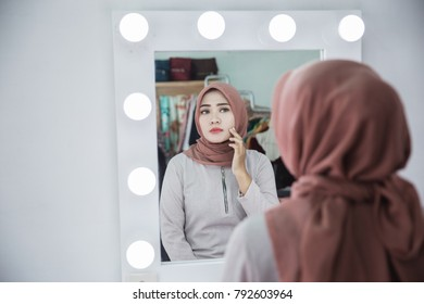unhappy muslim woman with hijab looking at her face in the mirror
