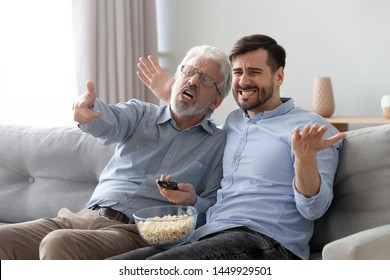 Unhappy old father and son watching tv show or movie together, eating popcorn snack, sitting on couch at home, angry fans discussing, disappointed by bad football or soccer match result, goal