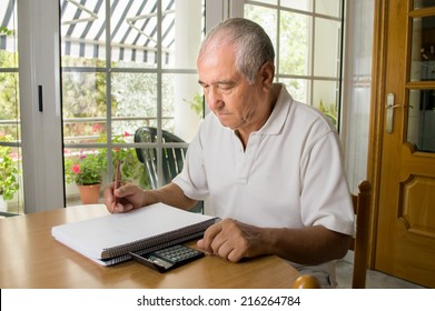 Unhappy old man calculating the monthly expenses at home