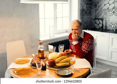 unhappy old man is waiting for his relatives. gey-haired man is celebrating Chritmas alone.