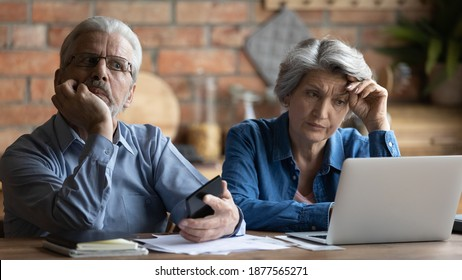 Unhappy older senior family couple thinking of financial problems, feeling stressed of banking debt notification or not enough money while calculating budget together at home, bankruptcy concept.