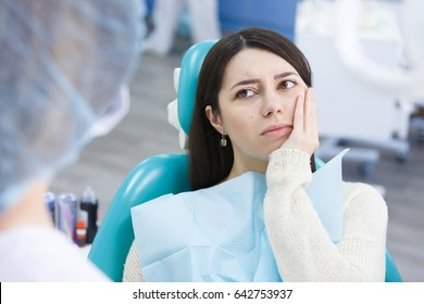 Unhappy patient having a toothache in dental clinic in professional chair