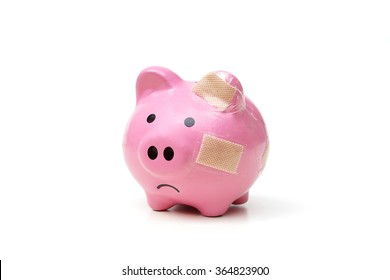 An unhappy pink piggy bank with bandages
