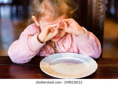 Unhappy preschooler girl doesn't want to eat