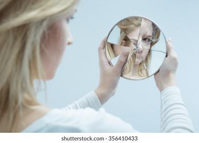 Unhappy pretty girl with complexes and broken mirror