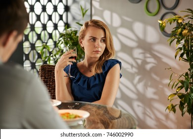 Unhappy pretty young woman drinking wine during blind date in restaurant