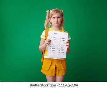 unhappy pupil with backpack holding a bad grade test isolated on green background