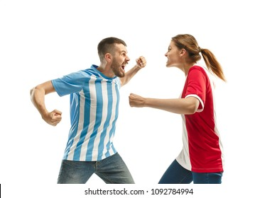The unhappy and sad Argentinean fan on white background. The young man in soccer football uniform and girl at white studio. Fan, support concept. Human emotions concept.