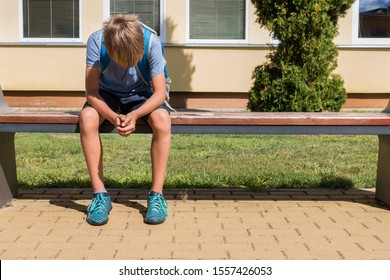 Unhappy sad boy sitting in closed position with his head down. School bullying, learning difficulties concept