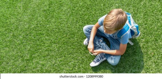 Unhappy sad upset boy sitting alone on the grass
