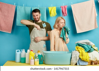 unhappy sad young man and woman in aprons are allergic to washing powder, soap, bad detergent. couple expressing negative emotion while doing laundry.what awful smell
